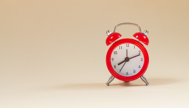 Red vintage alarm clock side view with copy space Premium Photo