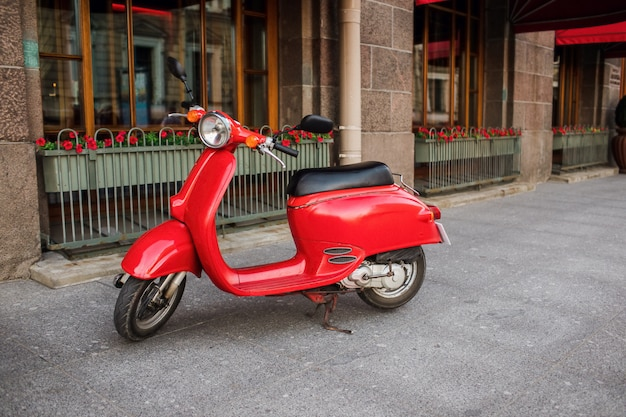 Red vintage scooter parked on sidewalk of empty city street. Premium Photo