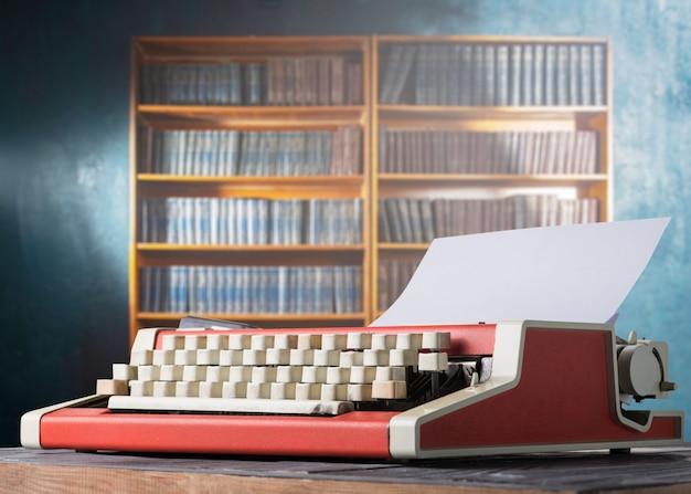 Красная винтажная пишущая машинка и книжная полка Premium Фотографии