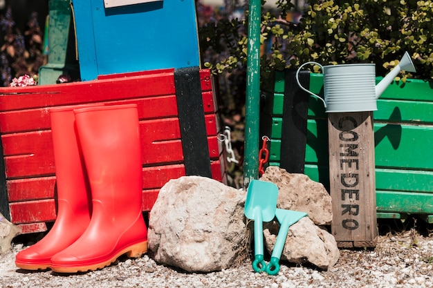 Red wellington boots; watering can; gardening tools in the garden Free Photo