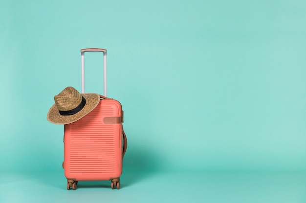 Red wheeled suitcase with hat Premium Photo