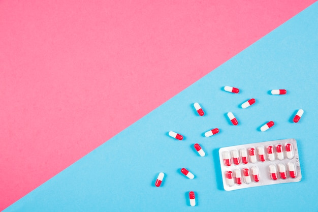 Red and white capsules on dual background Free Photo