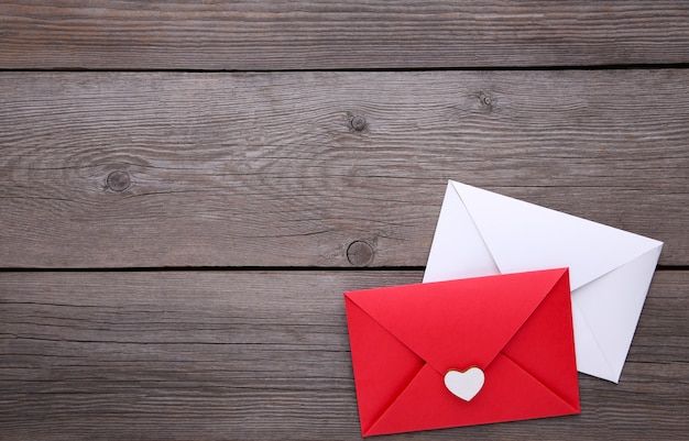 Red and white envelopes on grey background Premium Photo