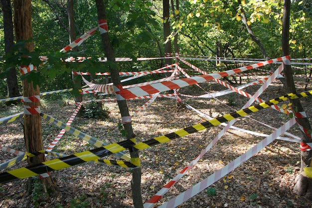 Red and white hazard tapes around the incident area in the park Premium Photo