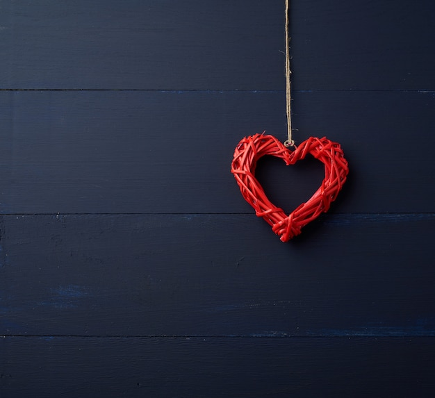 Red wicker decorative heart hanging on brown rope Premium Photo