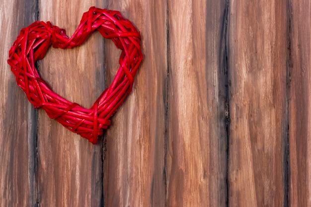 Red wicker heart on a wooden brown  . valentines day, love. copyspace Premium Photo