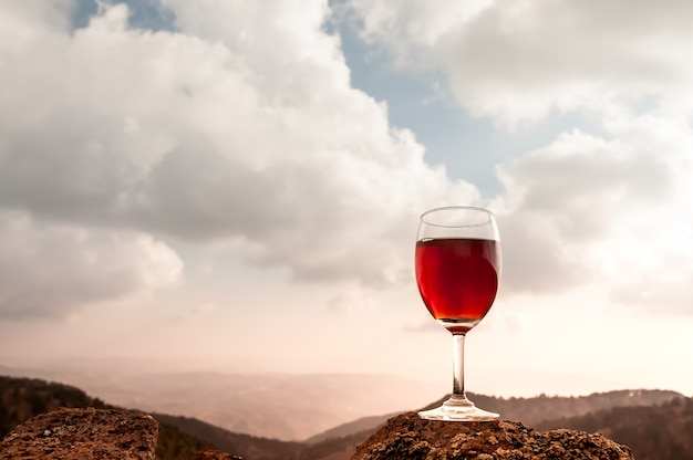 Red wine glass and beautiful autumn mountainscape Free Photo