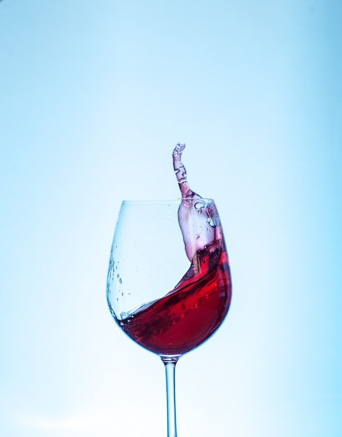 Red wine in the glass on a blue background. the concept of beverages and alcohol. Premium Photo