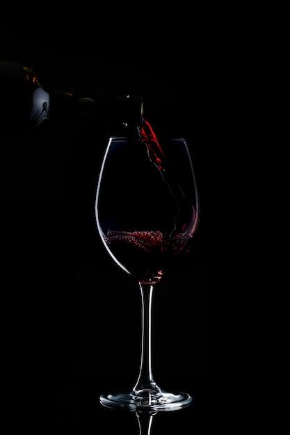 Il vino rosso viene versato al bicchiere con un lungo gambo nel buio Foto Gratuite