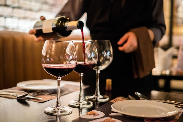 Red wine pouring into wine glass, close-up Premium Photo