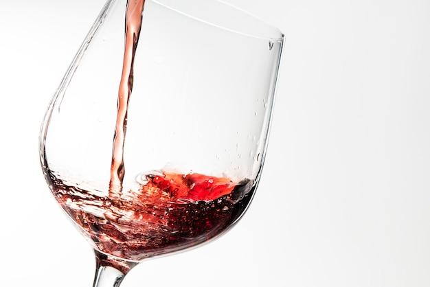 Vino rosso che versa in un bicchiere di vino Foto Gratuite