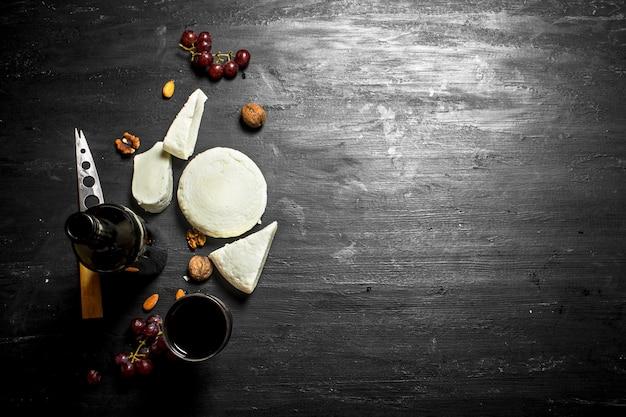 Красное вино со свежим овечьим сыром и виноградом. на черном деревянном фоне Premium Фотографии