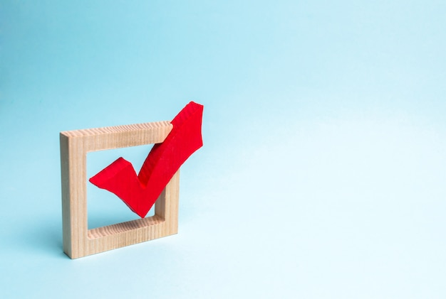 Red wooden checkmark for voting on elections on a blue background. Premium Photo