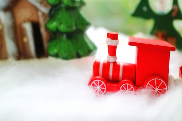 The red wooden train running on snow with pine tree and wooden house. Premium Photo