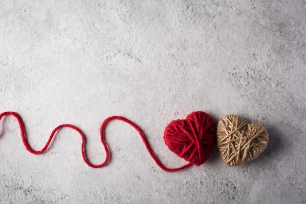 벽 배경에 모양의 빨간색 원사 심장 무료 사진