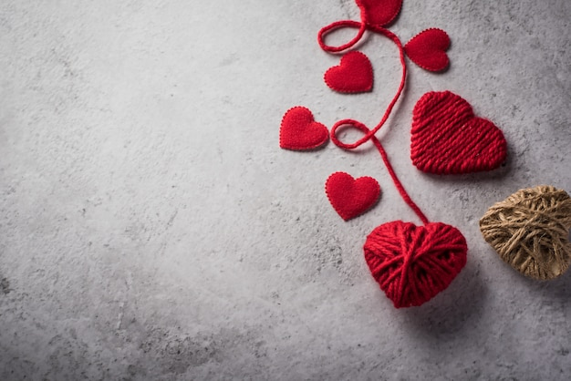 Red yarn heart shaped on the wall background Free Photo