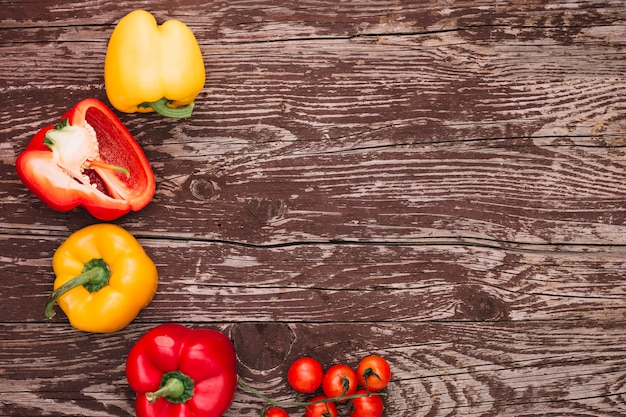Red and yellow bell peppers and cherry tomatoes over the wooden desk Free Photo