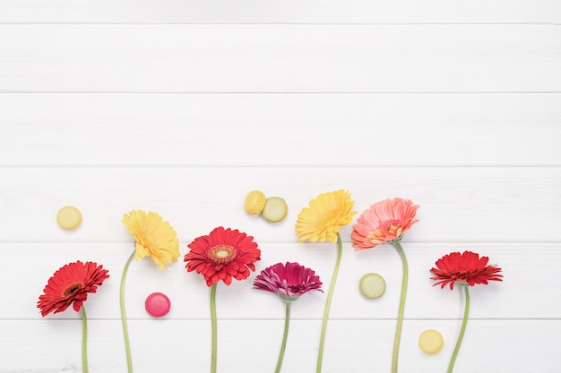 Red, yellow gerbera flowers and macaroons in wooden background. Premium Photo