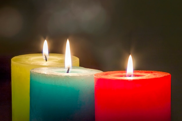 Red, yellow and green colourful candles with blurred bokeh background. christmas and new year copy space. Premium Photo