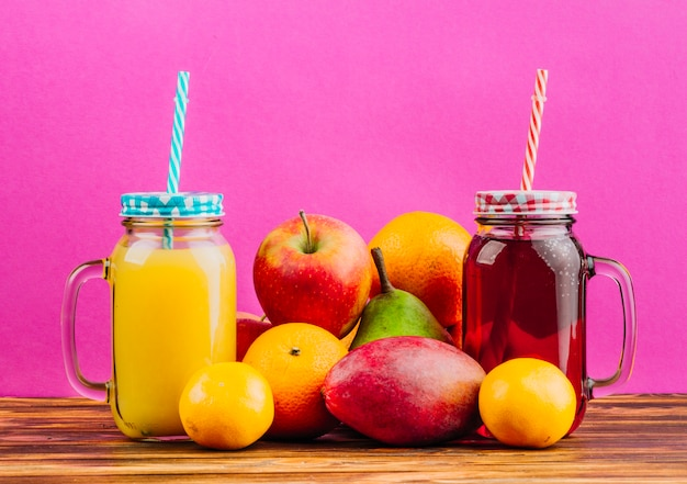 Red and yellow juice mason jars with drinking straws and fresh fruits against pink background Free Photo