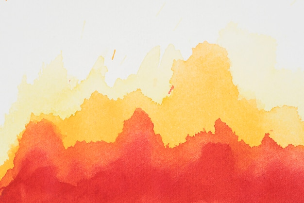 Red and yellow mix of paints on white paper Free Photo