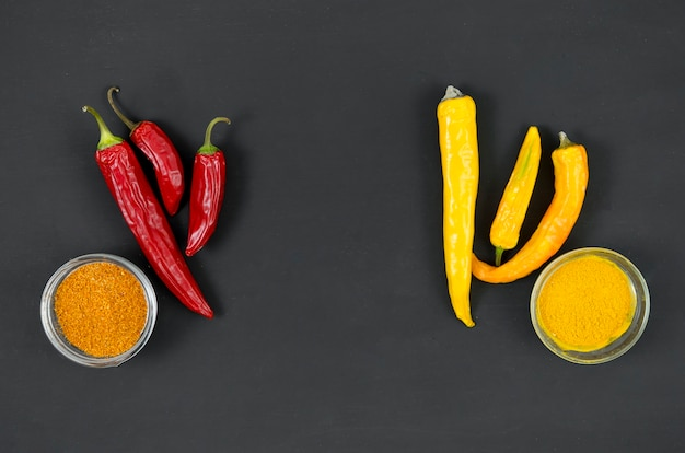 Red and yellow peppers on a grey background top view Free Photo
