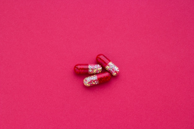 Red and yellow pills on a claret background, close-up Premium Photo