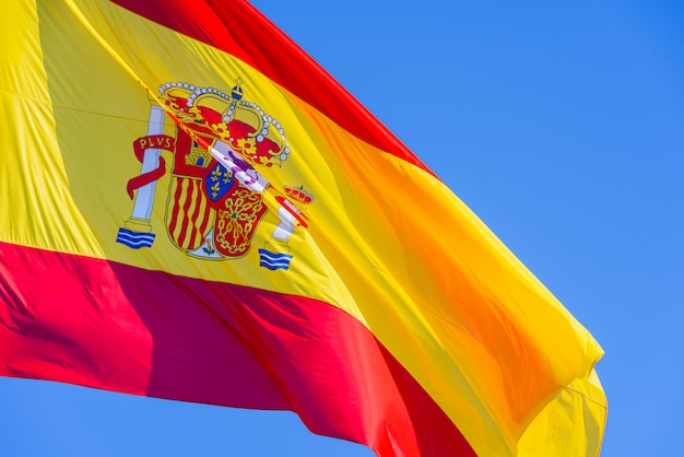 Red and yellow spain flag with royal shield waving in the wind isolated against blue sky Premium Photo