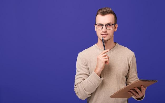物思いにふける男redactorは手に茶色の紙のノートと顔の近くに黒いボールペンで立っています。 Premium写真