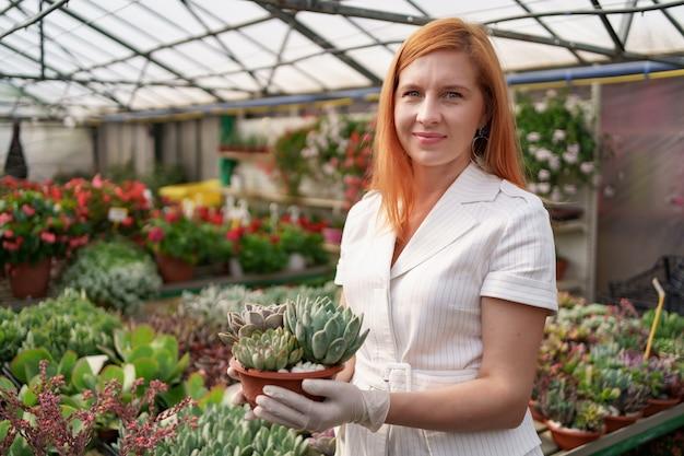 Ritratto di donna rossastra che indossa guanti di gomma e vestiti bianchi che tengono piante grasse o cactus in vaso con altre piante verdi Foto Gratuite