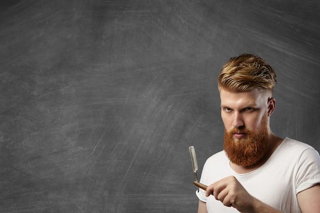 Рыжий парикмахер со стильной стрижкой и хипстерской бородой держит свой аксессуар для парикмахерской - старинную опасную бритву. Бесплатные Фотографии