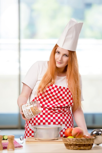 Redhead cook working in the kitchen Premium Photo