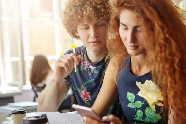 Рыжая женщина и мужчина сидят вместе в окружении копировальных книг Бесплатные Фотографии