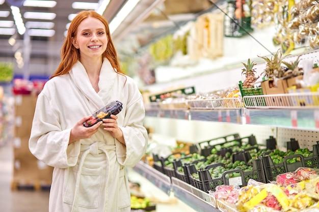 빨간 머리 여성은 목욕 가운을 입고 손에 포장 된 야채를 보유하고 있습니다. 슈퍼마켓에서 프리미엄 사진