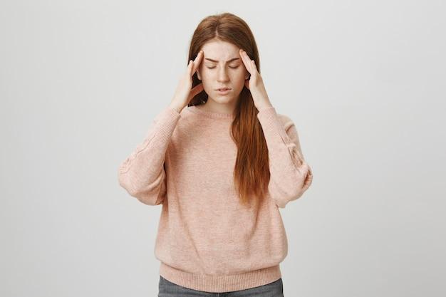 Рыжая студентка страдает от мигрени Бесплатные Фотографии