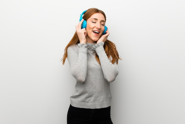 Redhead girl over white wall listening to music with headphones Premium Photo