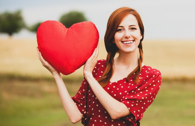 Redhead girl with toy heart at meadow near wheat field Premium Photo