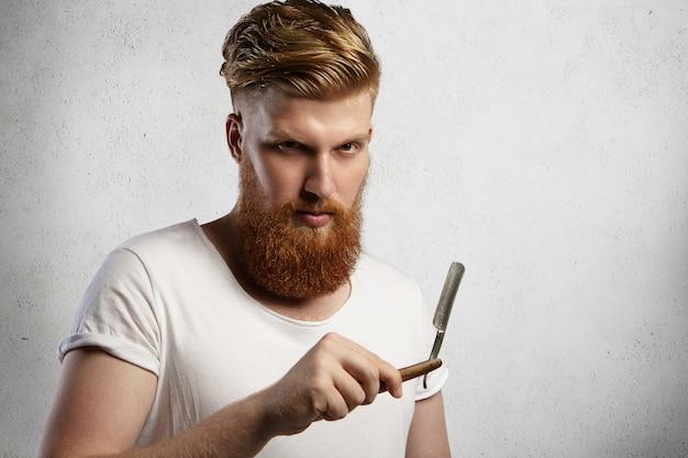 赤毛の美容師または理髪店で白いtシャツを着たファジーなひげを生やした理髪店。理髪店で彼のストレートエッジのかみそりの鋭い刃を示し、クライアントを剃る準備ができています。 無料写真