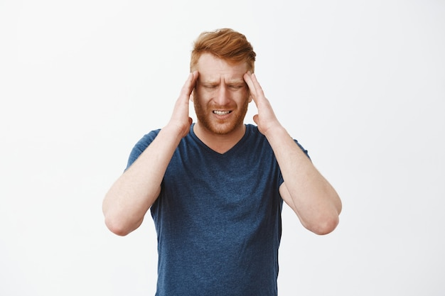 Рыжий мужчина-предприниматель с рыжими волосами, касающимися висков, хмурется и гримасничает от болезненной головной боли, ощущения головной боли или мигрени Бесплатные Фотографии