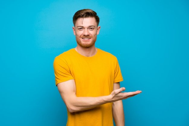 Redhead man over blue wall presenting an idea while looking smiling towards Premium Photo