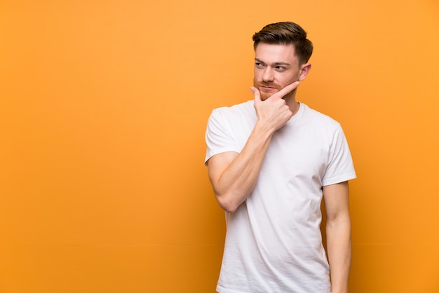 Redhead man over brown wall thinking Premium Photo