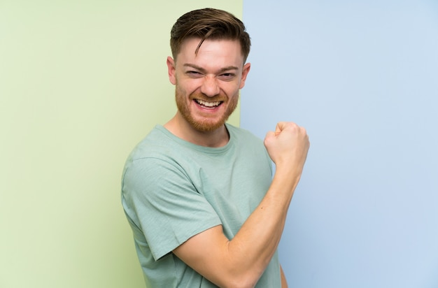 Redhead man over colorful wall celebrating a victory Premium Photo