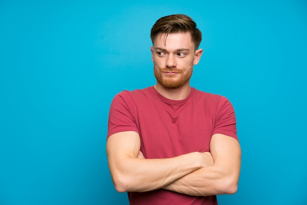 Redhead man on isolated blue wall standing and thinking an idea Premium Photo