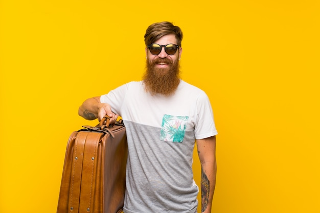 Redhead man with long beard holding a vintage briefcase smiling a lot Premium Photo