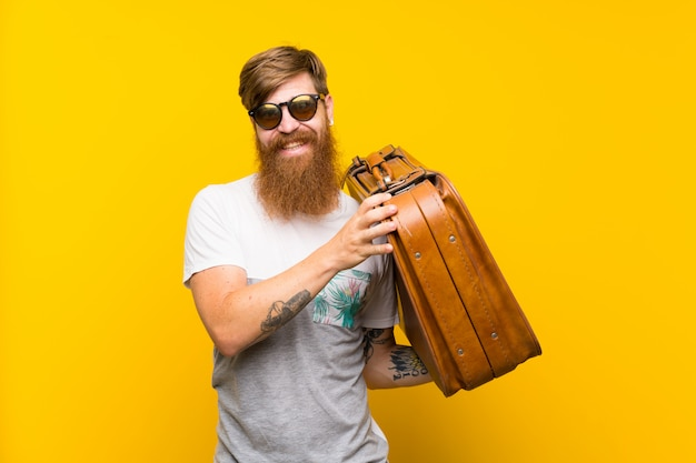 Redhead man with long beard holding a vintage briefcase Premium Photo