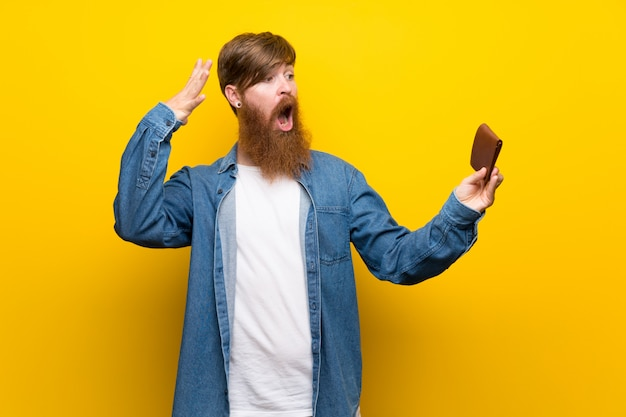 Redhead man with long beard over isolated yellow wall holding a wallet Premium Photo