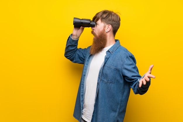 Redhead man with long beard over isolated yellow wall with black binoculars Premium Photo