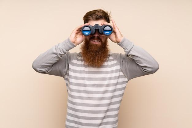黒双眼鏡で孤立した背景に長いひげを持つ赤毛の男 Premium写真