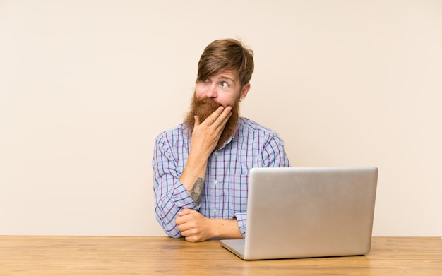 Redhead man with long beard in a table with a laptop thinking an idea Premium Photo