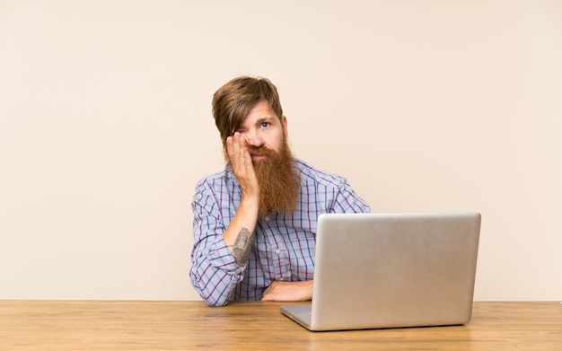 Redhead man with long beard in a table with a laptop unhappy and frustrated Premium Photo